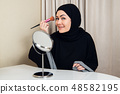 Arab woman applying makeup on her face, wearing traditional Arabian dress 48582195