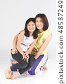 Mother and daughter on gray background . 48587249