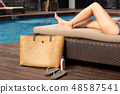 Beautiful woman legs lying on sunbed with beach bag and sunscreen and sandal. 48587541