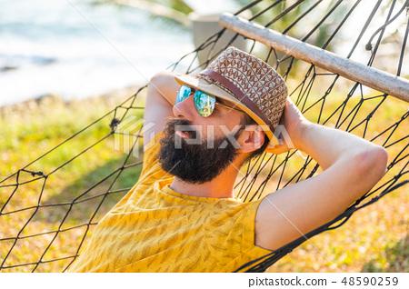 Bearded guy resting in a hammock by the ocean 48590259
