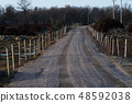 Gravel road with fence and snow stakes 48592038