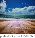 wooden table on the beach with sea backgroung 48593263
