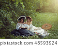 Two beautiful girls are reading a book in nature 48593924