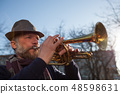 elderly musician plays in the street on a trumpet  48598631