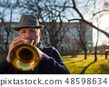 elderly musician plays in the street on a trumpet  48598634