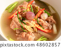 Hot and spicy soup with pork ribs in white cup . 48602857