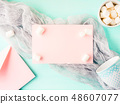 Pink card and marshmallows on turquoise 48607077