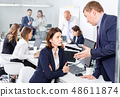 Outraged manager expressing dissatisfaction with work of frustrated young woman in modern office 48611874