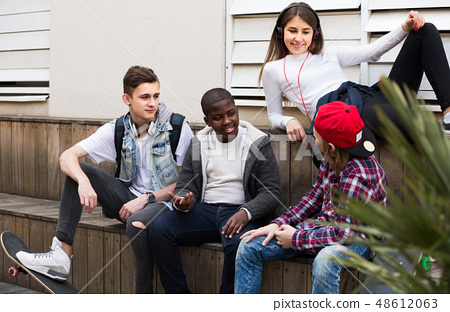girl and three boys hanging out outdoors and discussing something 48612063