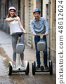 Laughing tourists going sightseeing by segways 48612624
