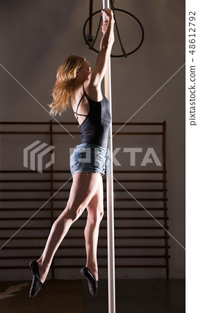 Sexy girl in denim shorts performs a dance with a pylon 48612792