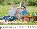 Smiling family of four having a picnic outdoors 48613720