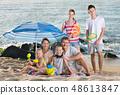 Parents children under sun umbrella 48613847