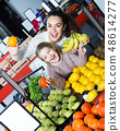 Happy mother and daughter buying ripe fruits 48614277