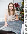 Woman serving festive table with tablecloth 48614387