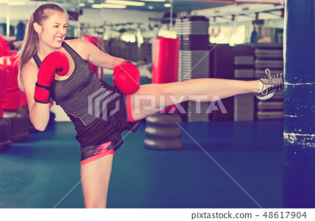 Woman boxer is training kick in box gym. 48617904