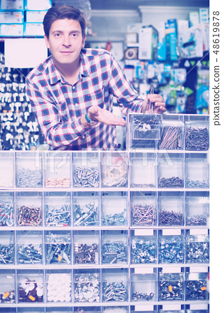 Employee selling nuts, screw and fasteners 48619878