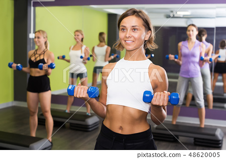 Females exercising aerobics with dumbbells at gym 48620005