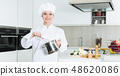 Cheerful woman chef preparing food with whisk on kitchen 48620086