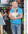 Portrait of young man with small dog standing in pet store 48620359