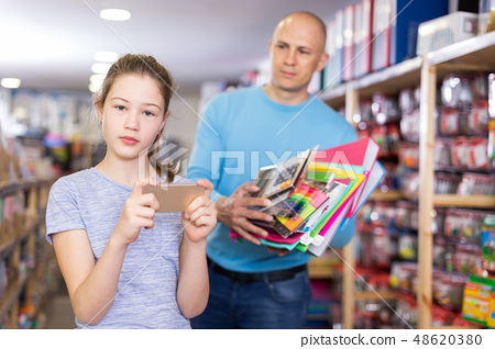 girl absorbed in phone while dad choosing stationery 48620380
