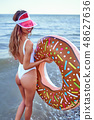 Woman in swimsuit with swim ring 48627636