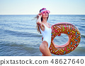 Woman in swimsuit with swim ring 48627640