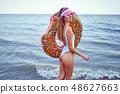 Woman in swimsuit with swim ring 48627663