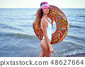 Woman in swimsuit with swim ring 48627664