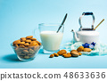 Almond milk in a glass against blue background 48633636