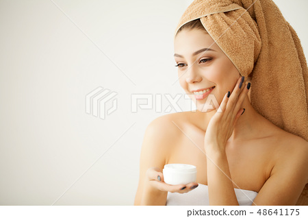 Young Spa Model with Clear Skin and Towel. Beautiful Spa Woman Applyng Monsturizing Cream. Skincare 48641175