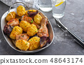 Roasted chicken leg with potatoes cumin and garlic on black background. Copy space. 48643174