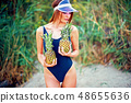Skinny model in swimsuit posing with pineapples 48655636