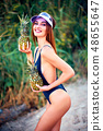 Skinny model in swimsuit posing with pineapples 48655647