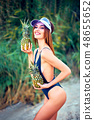 Skinny model in swimsuit posing with pineapples 48655652