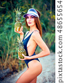 Skinny model in swimsuit posing with pineapples 48655654
