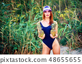 Skinny model in swimsuit posing with pineapples 48655655