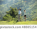 Man and woman playing golf on natural golf course 48665154