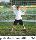 little happy boy on football field 48667266