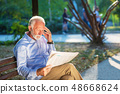 Portrait of a senior man reading newspapers in the park. 48668624