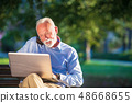 Business correspondence. Focused mature businessman using laptop while sitting in park 48668655