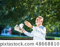 Senior man relaxing in park on a sunny day seated on a wooden bench and waiting for someone 48668810