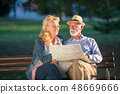 Portrait of happy man and woman reading map while sitting on a park bench. Senior couple on vacation 48669666