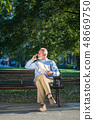 Smiling senior man talking on the phone while sitting on the bench in the park. 48669750