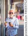 technology, people, lifestyle and communication concept - senior man texting message on smartphone 48669752