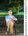 Senior man relaxing in park on a sunny day seated on a wooden bench and waiting for someone 48669753