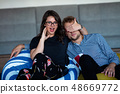 Portrait of an excited young couple relaxing on a couch at home while watching TV and eating popcorn 48669772