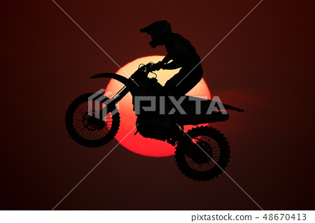 Silhouette of motocross jump in the air 48670413