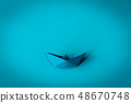 blue paper boat on blue textured background 48670748