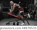 Handsome strong bodybuilder athletic men pumping 48676535
